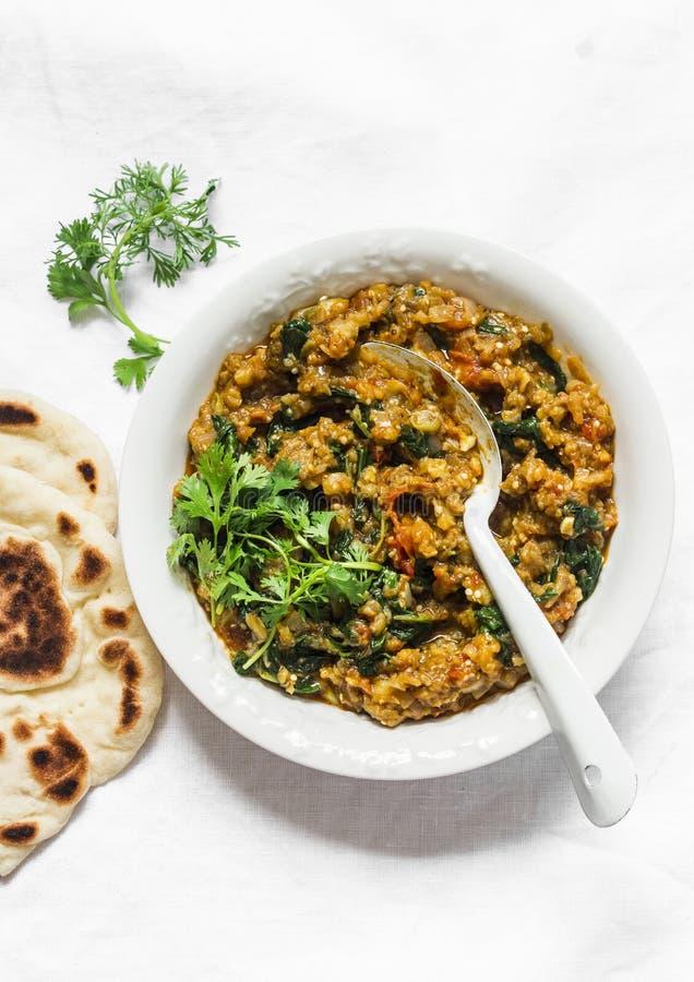 De vegetarische kerrie van de auberginespinazie met naan flatbread op een lichte achtergrond, hoogste mening Indische keuken royalty-vrije stock foto
