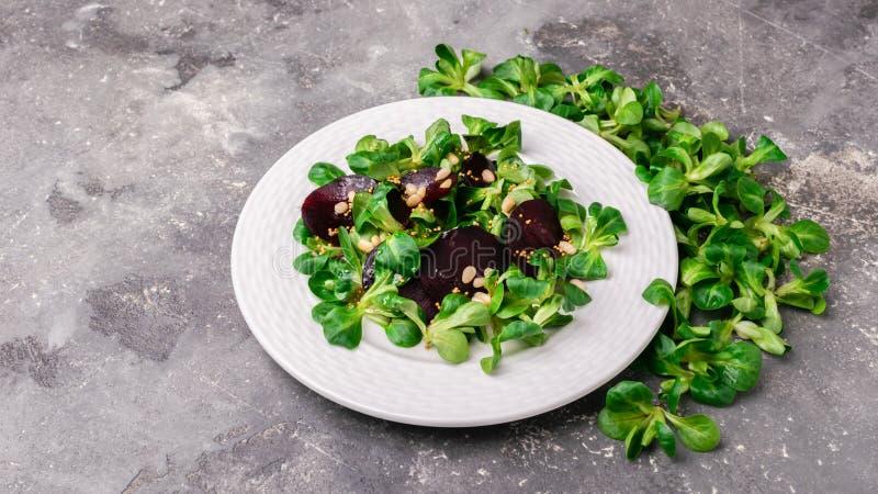 De vegetarische salade van verse ruwe bietengroenten en jonge spruiten van slawortel verlaat witte ronde plaat grijze achtergrond stock afbeelding