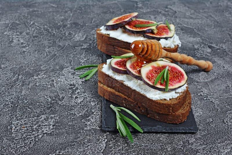 De vegetarische sandwich met fig., de zachte kaas, de honing en de rozemarijn op zwarte lei schepen in stock afbeeldingen