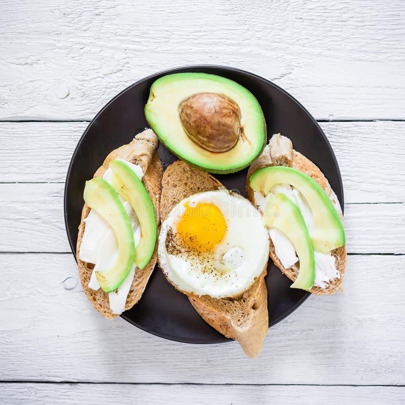 De vegetarische sandwiches met avocado en ei op dark plateren op houten lijst Vlak leg Hoogste mening Smakelijk voedselconcept stock afbeelding