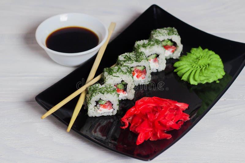 De vegetarische sushi rolt op een zwarte vierkante plaat met wasabi, sojasaus en gember Witte Houten Achtergrond royalty-vrije stock foto