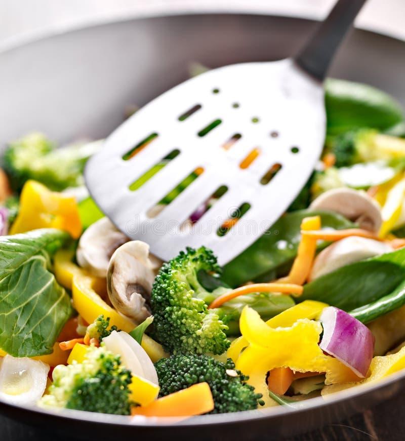 De vegetarische wok beweegt gebraden gerecht met metaalspatel. royalty-vrije stock afbeelding