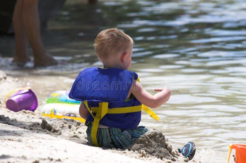 De veiligheid van het kind bij water stock afbeeldingen