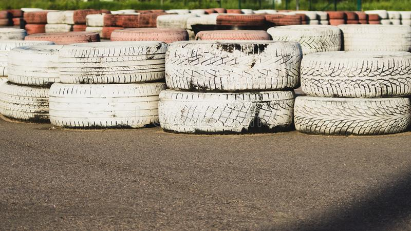 De veiligheidsbarrière van het rasspoor asfalt het rennen spoor met rode en witte banden De kleurrijke stapel van Banden karting  stock foto's