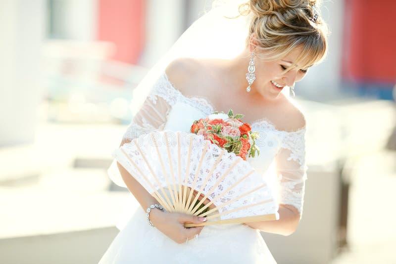 De ventilator van de bruidholding en huwelijksboeket, in openlucht stock afbeelding