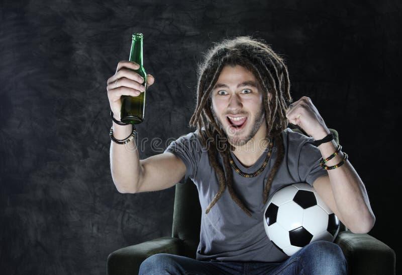De ventilator van de voetbal of van het voetbal het letten op televisie stock foto's