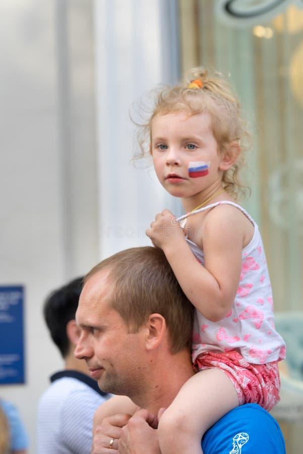 De ventilator van de meisjesport met Russische vlag op de wangzitting op haar vader` s schouders stock afbeelding
