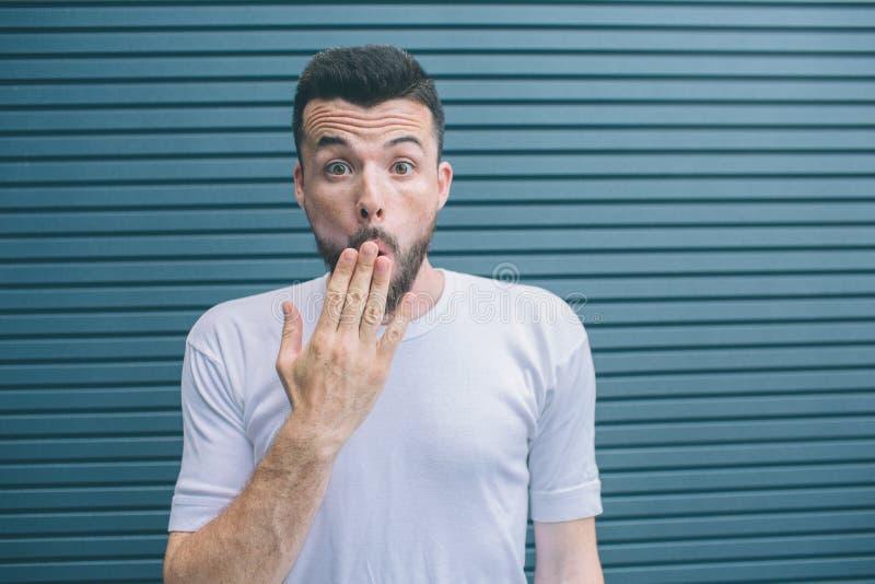 De verbaasde en opgewekte kerel kijkt op camera Hij behandelt mond met hand Geïsoleerd op gestreepte en blauwe achtergrond royalty-vrije stock foto