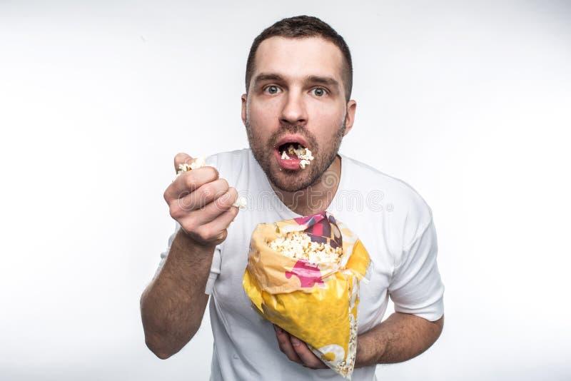 De verbaasde kerel houdt een klein pak van goede popcorn en eting het Hij heeft zijn mond geopend Hij eet zeer geen popcorn royalty-vrije stock foto's