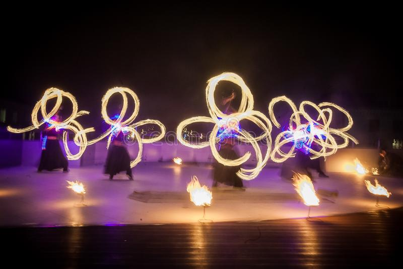 De verbazende brand toont dans Branddansers die in mooie kostuums met kleurrijke vlammen spelen stock fotografie