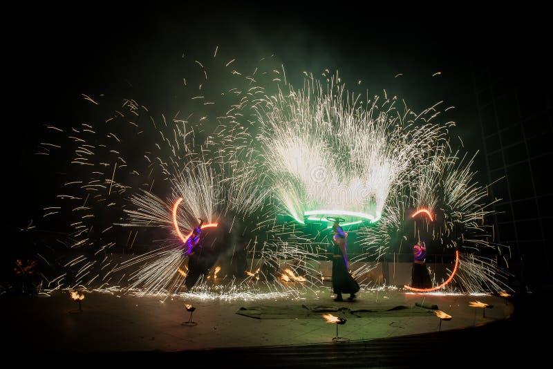 De verbazende brand toont dans Branddansers die in mooie kostuums met kleurrijke vlammen spelen stock afbeelding