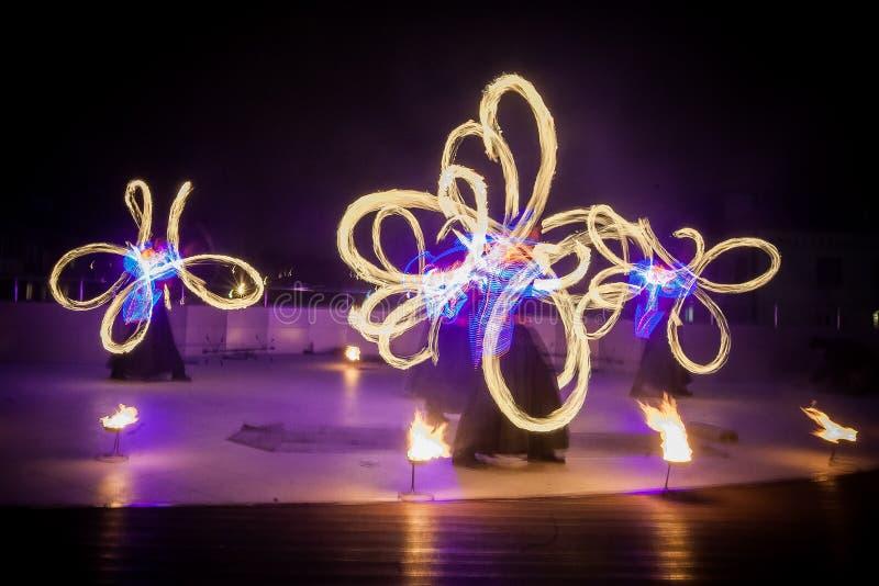 De verbazende brand toont dans Branddansers die in mooie kostuums met kleurrijke vlammen spelen stock afbeeldingen