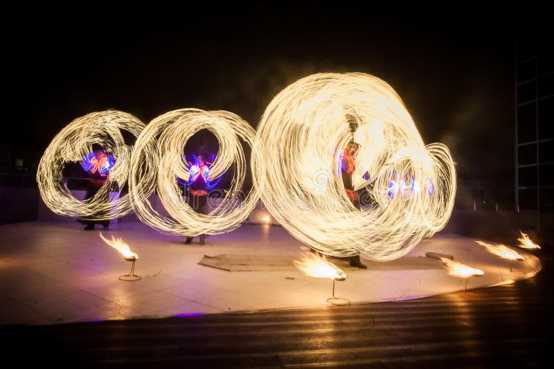 De verbazende brand toont dans Branddansers die in mooie kostuums met vlam spelen stock foto's