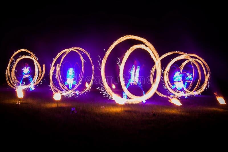De verbazende brand toont dans Branddansers die in mooie kostuums met vlam spelen stock afbeelding
