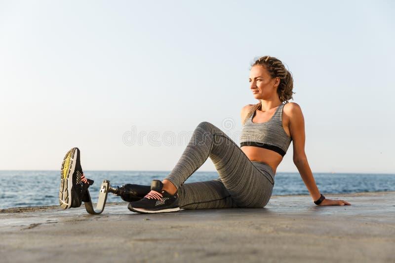De verbazende gehandicapte zitting van de sportenvrouw op het strand royalty-vrije stock fotografie