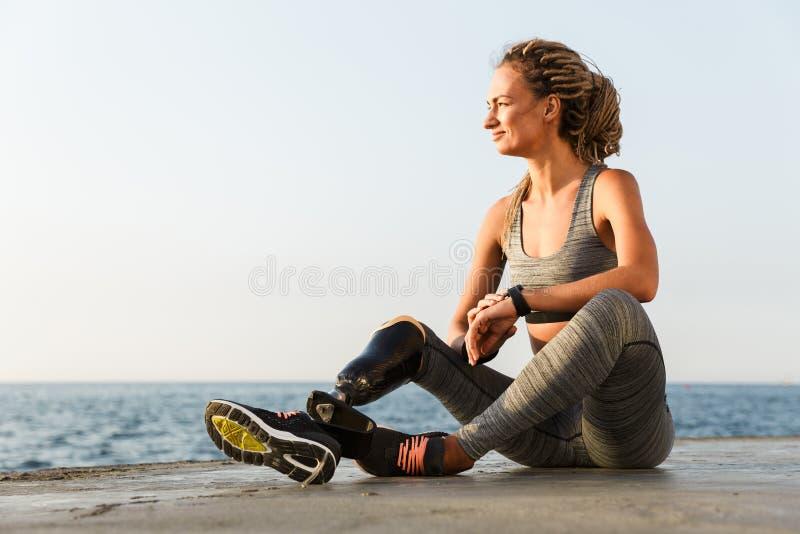 De verbazende gehandicapte zitting van de sportenvrouw op het strand royalty-vrije stock afbeeldingen