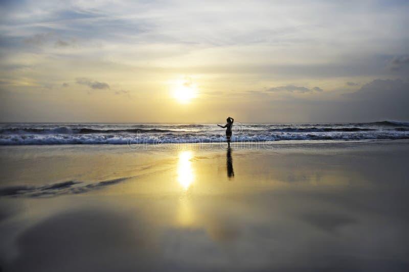 De verbazende mooie toneelmening van het zonsondergangstrand met silhouet van vrouw het kijken aan de oceaanhorizon onder een ora stock afbeeldingen