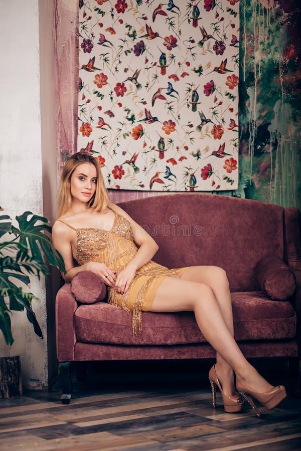 De verbazende vrouw van het luxeblonde in modieuze glanzende Gouden kleding en heldere make-up Het Portret van de manier Vierende stock afbeelding