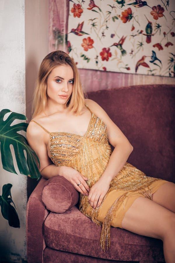 De verbazende vrouw van het luxeblonde in modieuze glanzende Gouden kleding en heldere make-up Het Portret van de manier Vierende royalty-vrije stock fotografie
