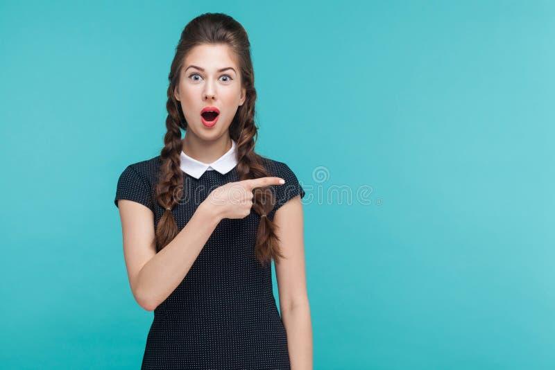 De verbazing, was vrouw benieuwd die vingerrecht richten, op exemplaarruimte stock foto