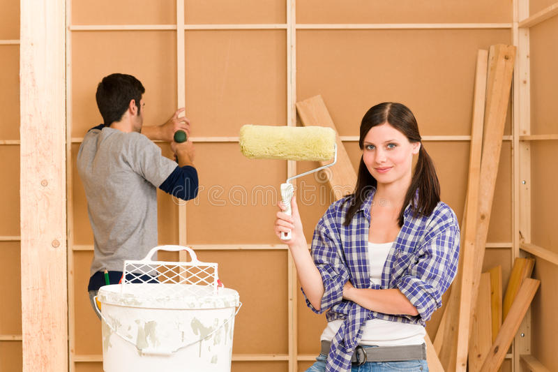 De verbetering van het huis: jong paar dat nieuw huis bevestigt royalty-vrije stock afbeelding