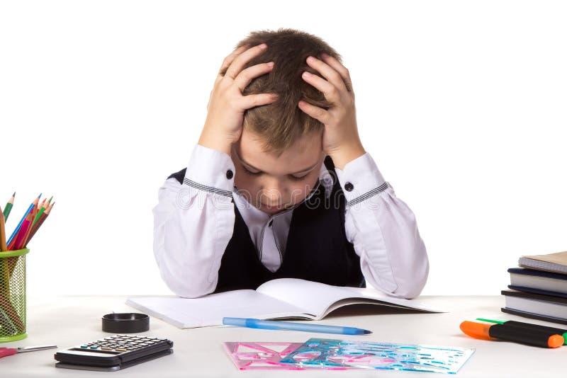 De verbijsterde leerlingszitting met verminderde die ogen bij het bureau met overhandigt het hoofd met kantoorbehoeften wordt omr royalty-vrije stock afbeelding