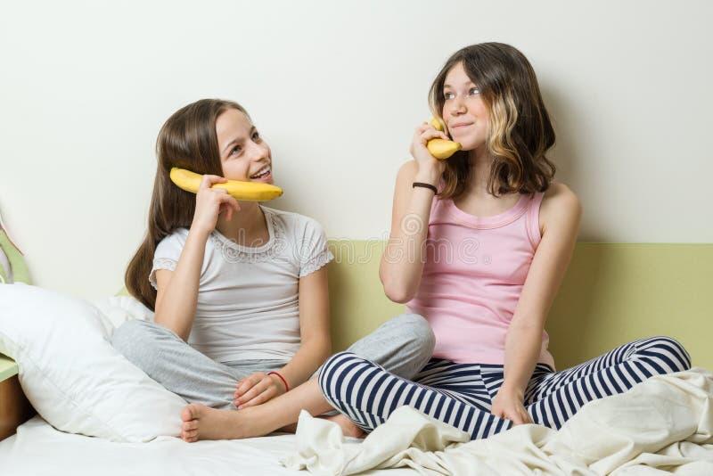 De verbinding, mededeling tussen mensen, meisjes speelt telefoon, bespreking met elkaar door een banaanpijp stock foto