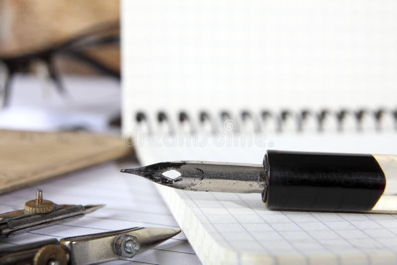 De verdelers en oude penholder met de pen liggen op de notitieboekjes die met de metaallentes worden genaaid op een houten lijst  royalty-vrije stock fotografie