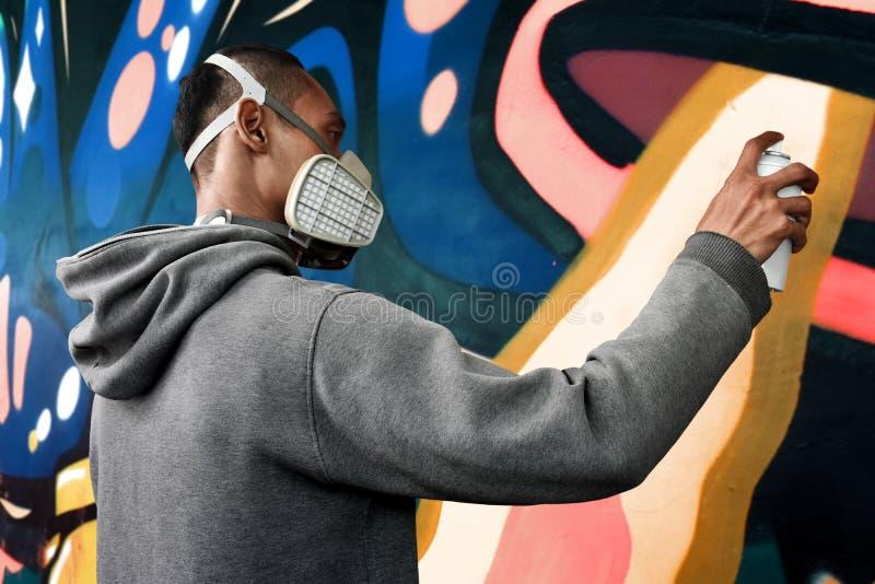 De verf van de graffitikunstenaar op de muur stock afbeelding
