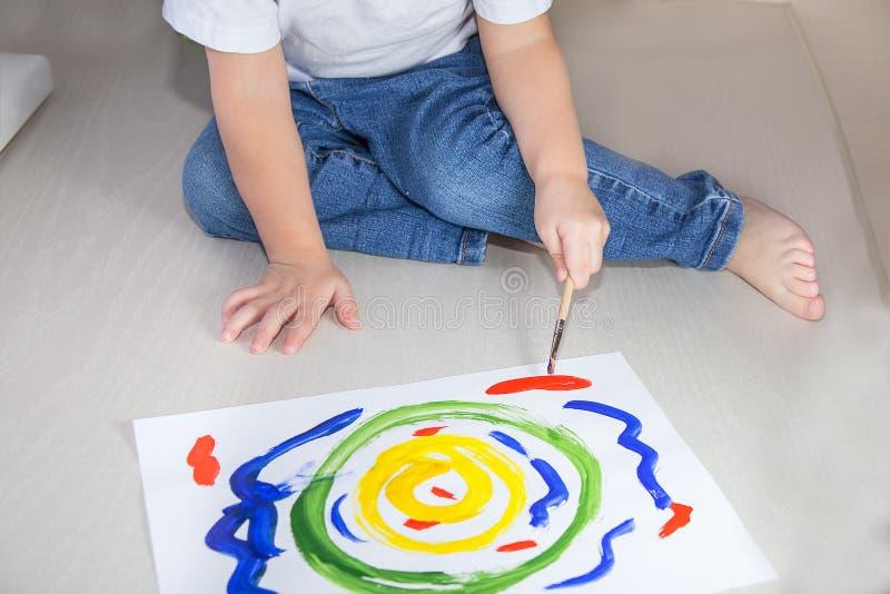 De verf, weinig jongen trekt thuis kleurrijke verven en een borstel stock afbeelding