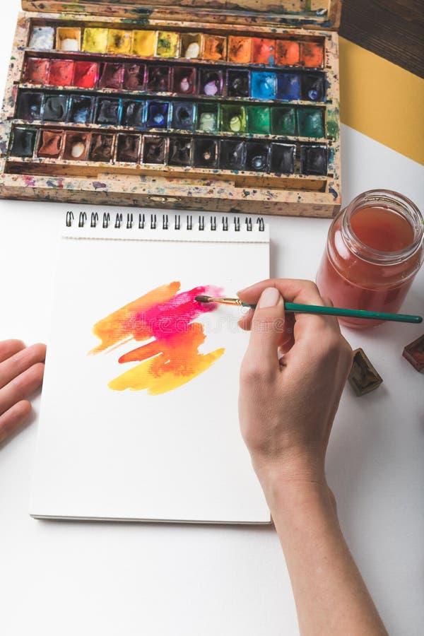 De verfborstel van de kunstenaarsholding en tekening het abstracte schilderen royalty-vrije stock foto