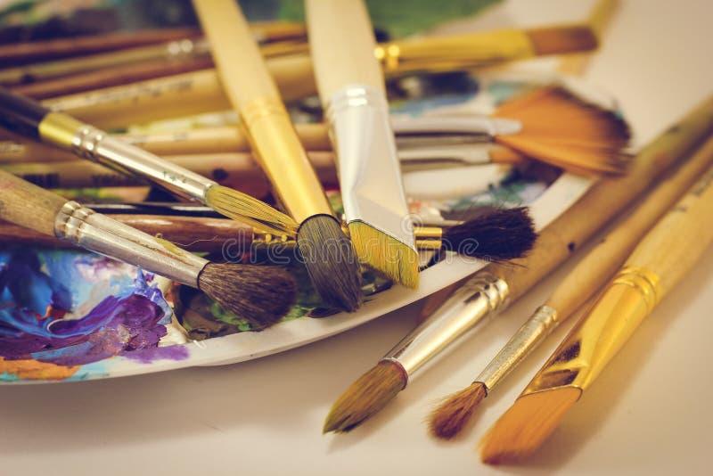De verfborstels en een palet liggen op de lijst, close-up stock afbeelding