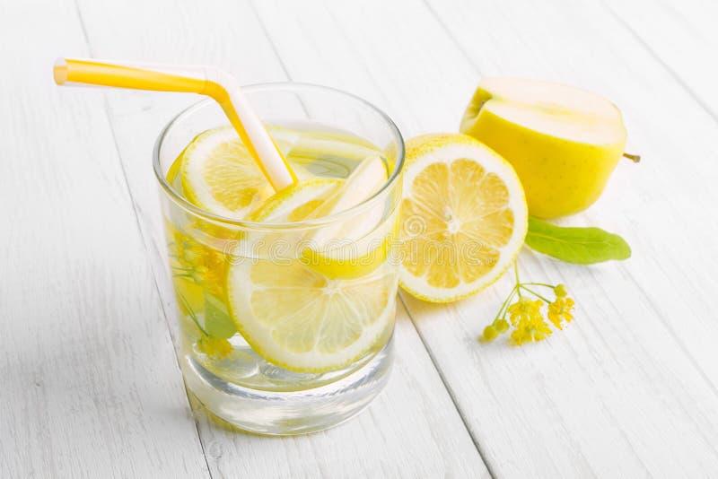De verfrissende drank voor ontgifting, citroenwater in een glas, verse appel en gele linde bloeit op een witte lijst stock afbeeldingen