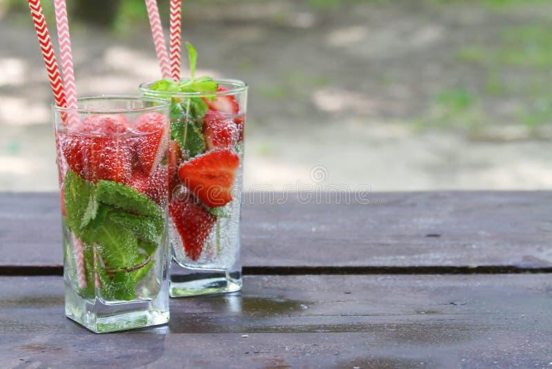 De verfrissende koude zomer drinkt Aardbei met munt in glas op houten lijst, openlucht stock foto