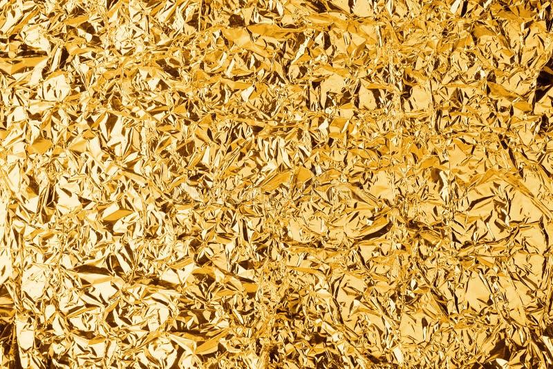De verfrommelde gouden achtergrond van de folie glanzende textuur, helder glanzend gouden luxeontwerp, metaal schittert oppervlak stock afbeeldingen