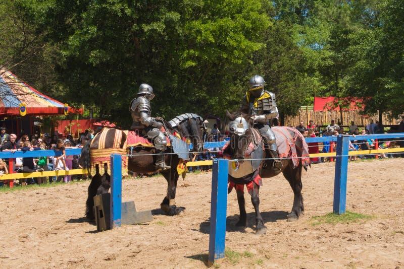 De vergadering dichtbij het midden van een arena, ridder twee treft voorbereidingen om bedelaars te doen royalty-vrije stock afbeelding