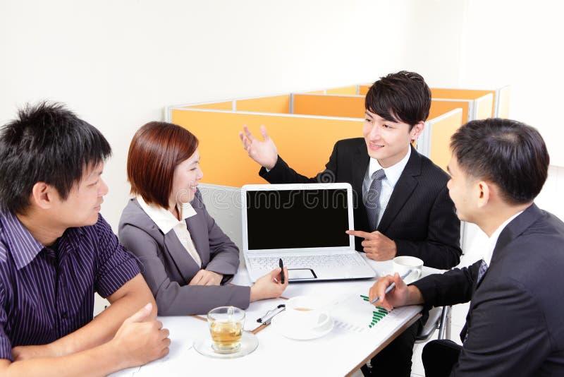De vergadering van de bedrijfsmensengroep met computer stock afbeelding