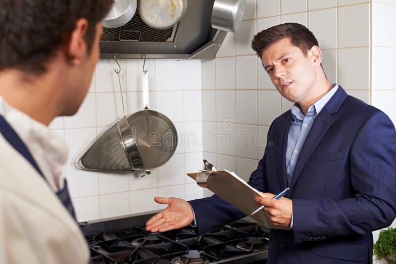 De Vergadering van de gezondheidsinspecteur met Chef-kok In Restaurant Kitchen stock afbeeldingen