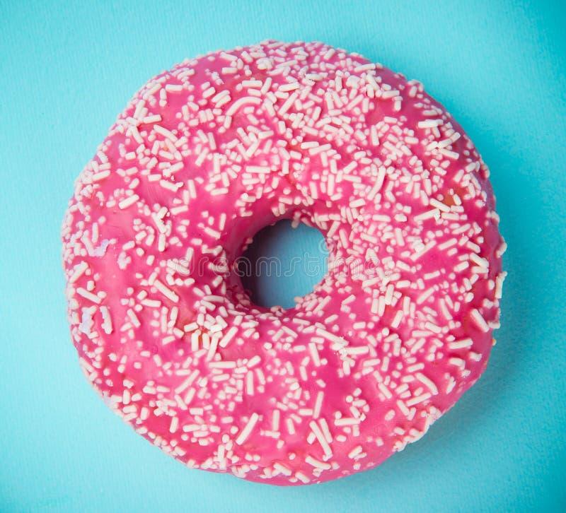 De verglaasde doughnut met kleurrijk bestrooit op blauwe pastelkleurachtergrond royalty-vrije stock afbeeldingen