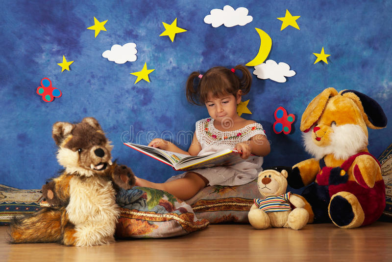 De verhalen van de meisjelezing aan haar gevulde stuk speelgoed vrienden royalty-vrije stock afbeelding