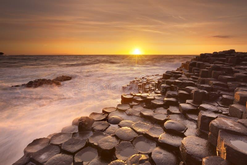 De Verhoogde weg van de Reus in Noord-Ierland bij zonsondergang royalty-vrije stock afbeelding