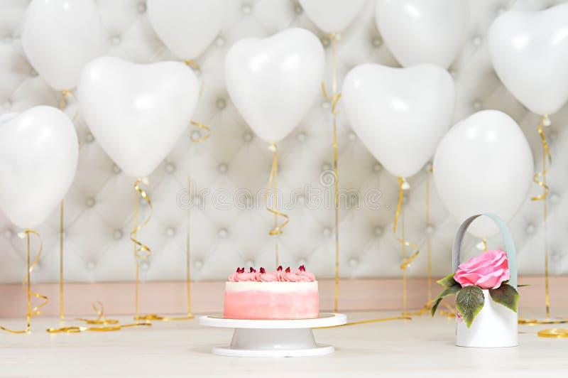 De verjaardagscake en hoort gestalte gegeven ballonsachtergrond stock fotografie