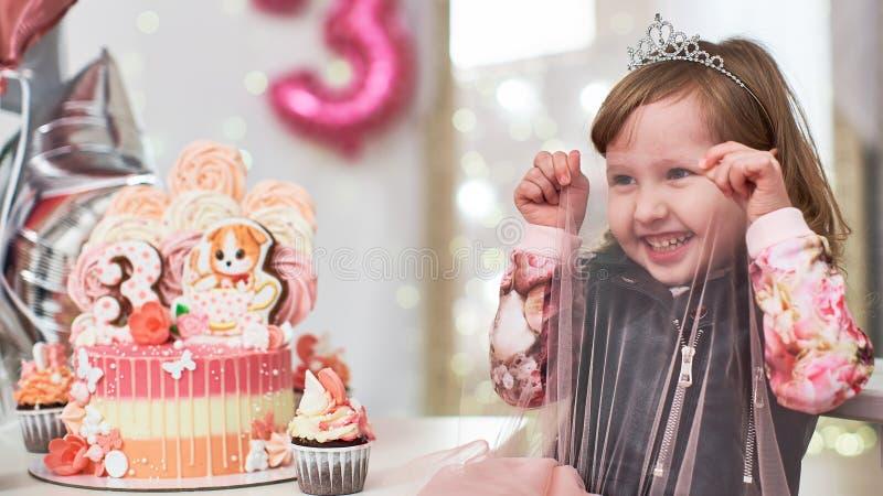 De verjaardagscake 3 jaar verfraaide met vlinders, peperkoekkatje met suikerglazuur en aantal drie bleek schuimgebakje - roze bin stock foto
