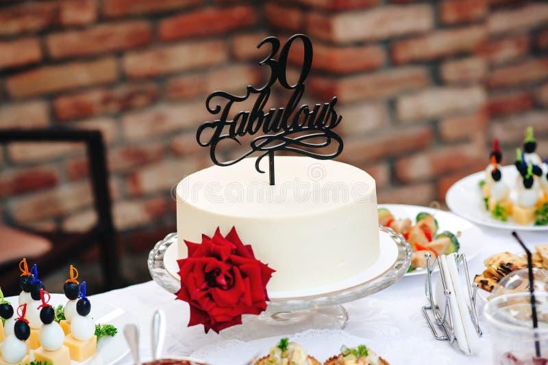 De verjaardagscake met rood nam toe Fabelachtige 30 Speciale oude cake 30 jaar Zoete lijst aangaande birhday partij openlucht Wit stock foto's
