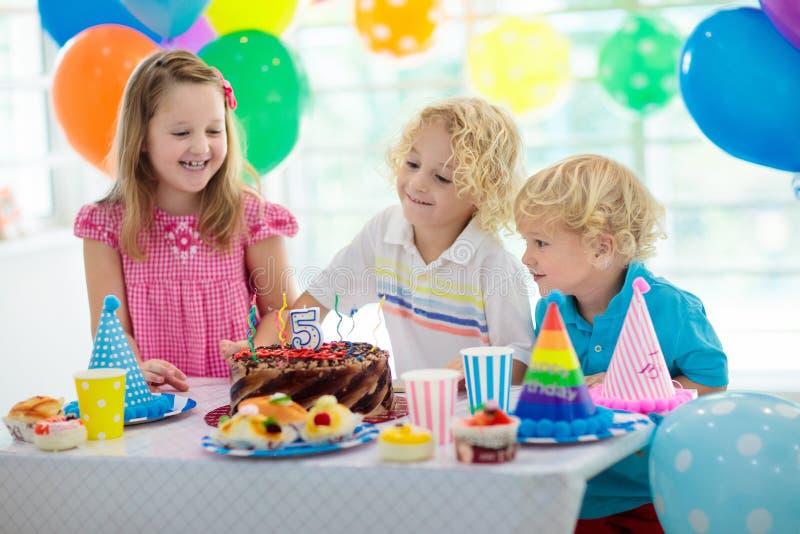 De verjaardagspartij van jonge geitjes Kind het blazen uit schouwt op kleurrijke cake Verfraaid huis met de banners van de regenb royalty-vrije stock foto