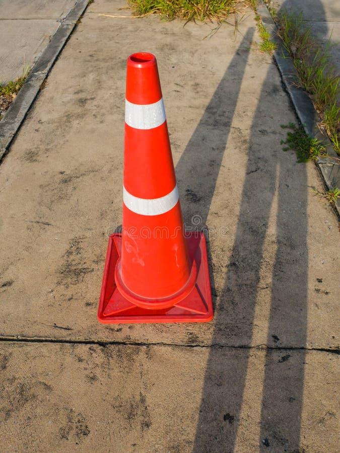 De verkeerskegel, met witte en oranje strepen op grijs asfalt, exemplaarruimte stock fotografie