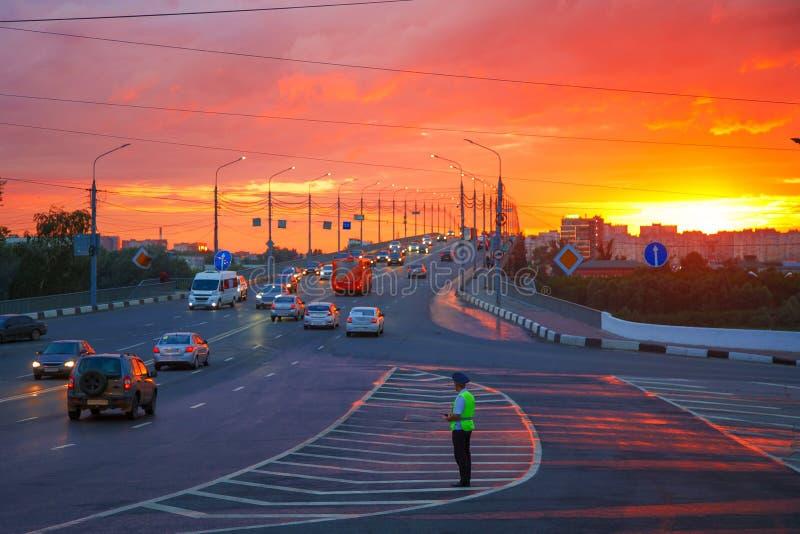 De verkeerspolitieman regelt verkeer op een bezige weg stock afbeelding