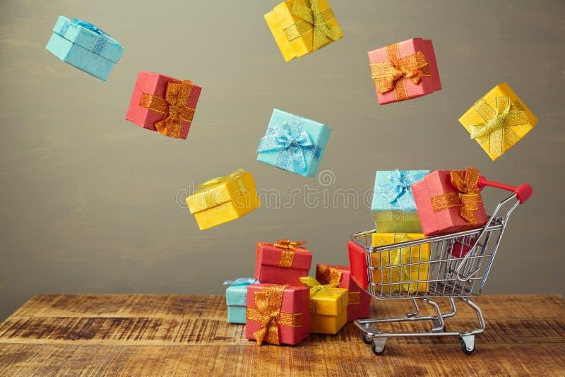 De verkoopconcept van de Kerstmiswinter met boodschappenwagentje en vliegende giftdozen stock fotografie