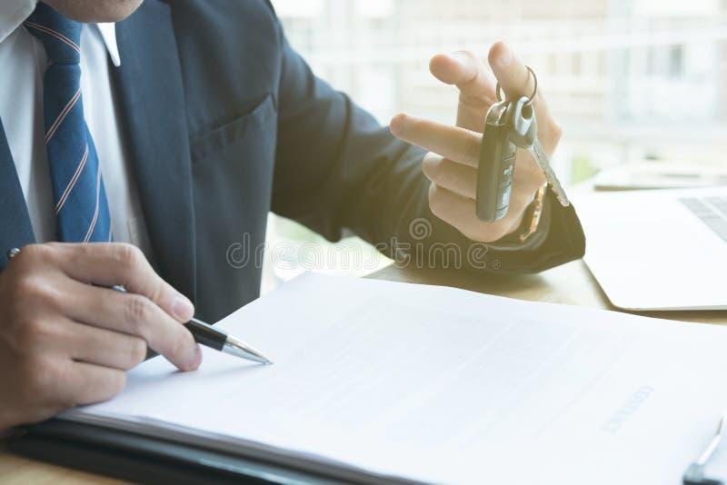 De verkoopcontract van het zakenmanteken met autosleutel op kantoor ownershi royalty-vrije stock afbeelding