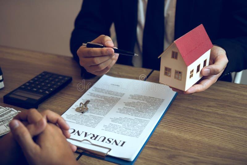 De de verkoopmakelaar van het bedrijfsmensenhuis gebruikt een pen die aan het huismodel richten en de diverse componenten van het stock foto's